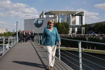 German Chancellor Angela Merkel crosses a footbridge over the river Spree in front of the Chancellery during a German Government 'Open Door Day' in Berlin August 25, 2013. REUTERS/Fabrizio Bensch