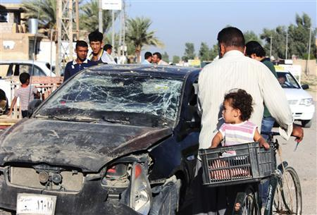 Residents pass by a damaged vehicle a day after a bomb attack in central Baquba, 65 km (40 miles) northeast of Baghdad, August 25, 2013. REUTERS/Mohammed Adnan