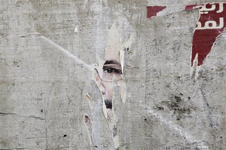 Remnants of a poster of ousted Egyptian President Mohamed Mursi are pictured on a wall on a street in Cairo August 25, 2013. REUTERS/Muhammad Hamed