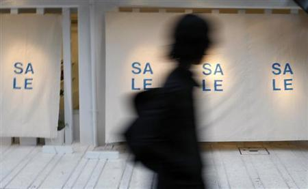 A passerby walks in front of a retail shop displaying sale advertisement in Tokyo March 27, 2009. REUTERS/Issei Kato