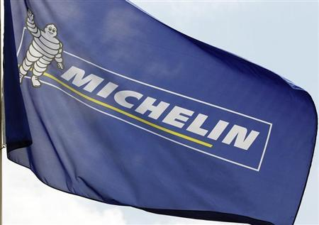 French tyremaker Michelin's flag with a Bibendum, the Michelin Man mascot, is pictured in front of the company's headquarters in Clermont Ferrand, central France, July 10, 2013. REUTERS/Regis Duvignau