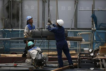 Workers hoist steel bars at a construction site in Tokyo August 12, 2013. REUTERS/Issei Kato