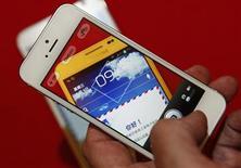 Мужчина фотографирует Samsung Galaxy Note на свой iPhone 5 в Пекине 5 июня 2013 года. Если, листая рекламный проспект, вам попалось на глаза что-то интересное, что бы вы хотели приобрести, то с новым приложением для iOS сделать это стало намного проще: достаточно просто сфотографировать понравившуюся вещь. REUTERS/Barry Huang/Files