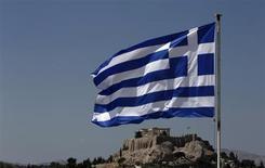 Греческий флаг на фоне Акрополя в Афинах 21 августа 2013 года. Греции может понадобиться дополнительная поддержка от партнеров по еврозоне в размере 10 миллиардов евро, но она не ждет, что помощь будет сопровождаться дополнительными условиями, сказал министр финансов в интервью газете Proto Thema в воскресенье. REUTERS/John Kolesidis