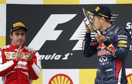 Red Bull Formula One driver Sebastian Vettel of Germany (R) celebrates winning the Belgian F1 Grand Prix beside second-placed Ferrari Formula One driver Fernando Alonso of Spain at the Circuit of Spa-Francorchamps August 25, 2013. REUTERS/Francois Lenoir