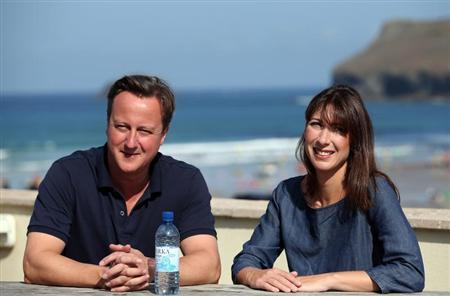 Britain's Prime Minister David Cameron and his wife Samantha pose for a photograph outside a cafe overlooking the beach, during their summer holiday, in Polzeath, south west England August 20, 2013. REUTERS/Matt Cardy/Pool