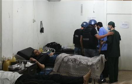 U.N. chemical weapons experts visit a hospital where wounded people affected by an apparent gas attack are being treated, in the southwestern Damascus suburb of Mouadamiya, August 26, 2013. REUTERS-Abo Alnour Alhaji