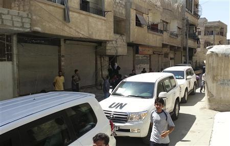 Residents gather around a convoy of U.N. vehicles carrying a team of U.N. chemical weapons experts at one of the sites of an alleged poison gas attack in the southwestern Damascus suburb of Mouadamiya, August 26, 2013. REUTERS-Abo Alnour Alhaji