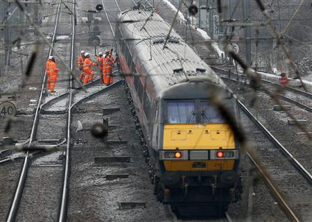 Network Rail workers remove fallen cables from an East Coast mainline train in Huntingdon, south-east England December 21, 2010. REUTERS/Darren Staples