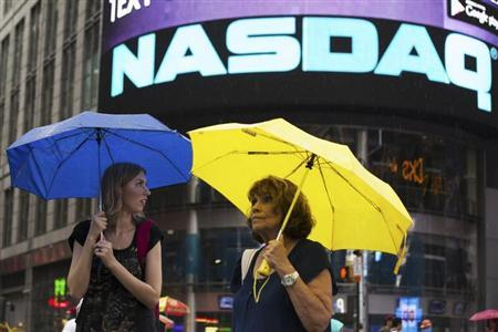 Two women hold umbrellas as they walk past the Nasdaq MarketSite in New York's Times Square, August 22, 2013. REUTERS/Lucas Jackson