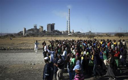 Miners chant slogans as they march past the Lonmin mine during the one-year anniversary commemorations to mark the killings of 34 striking platinum miners shot dead by police outside the Marikana platinum mine in Rustenburg, 100 km (62 miles) northwest of Johannesburg, August 16, 2013. REUTERS/Siphiwe Sibeko