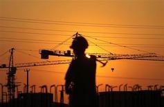 Рабочий на фоне строительных кранов в городе Наньтун в китайской провинции Цзянсу 6 августа 2013 года. Замминистра финансов Китая Чжу Гуанъяо сказал, что не видит необходимости стимулировать вторую мировую экономику и считает, что рост лучше поддержать структурными реформами. REUTERS/China Daily