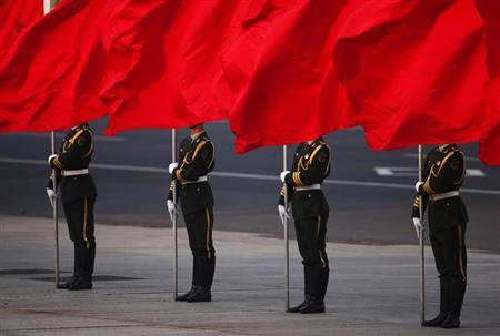 Soldiers of the People's Liberation Army's guard of honour hold flags in front of Beijing's Tiananmen Square during the official welcoming ceremony for Serbian President Tomislav Nikolic outside the Great Hall of the People in Beijing August 26, 2013. REUTERS/Petar Kujundzic