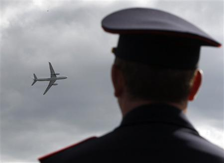 A spectator watches an airplane fly at the MAKS International Aviation and Space Salon in Zhukovsky outside Moscow August 27, 2013. REUTERS/Maxim Shemetov