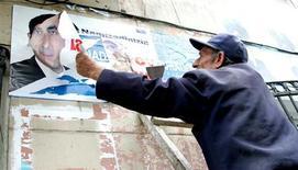 Рабочий сдирает со стены здания в Баку избирательные плакаты 6 ноября 2005 года. ЦИК Азербайджана во вторник не зарегистрировал главу оппозиционного Национального совета демократических сил (НСДС) Рустама Ибрагимбекова кандидатом в президенты из-за его российского гражданства, в ответ он собрался судиться. REUTERS/Jeyhun Abdulla/Str