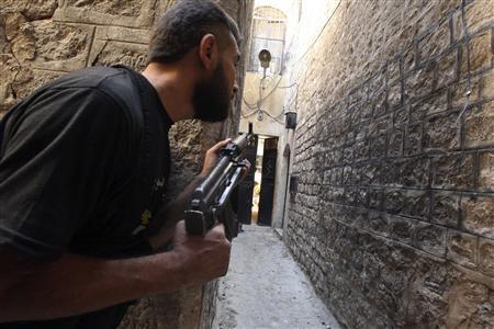 A Free Syrian Army fighter holds his weapons as he peeks at an alleyway in al-Jdeideh neighbourhood in the old city of Aleppo August 27, 2013. REUTERS/Ammar Abdullah