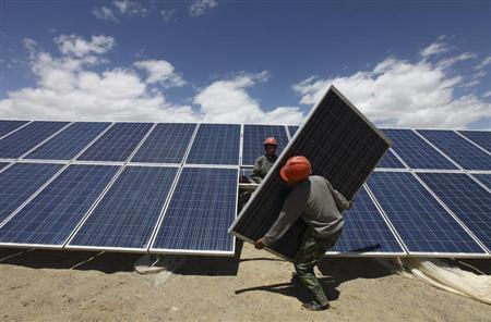 Workers install a solar panel in Jiuquan, Gansu province, July 14, 2013. REUTERS/Stringer