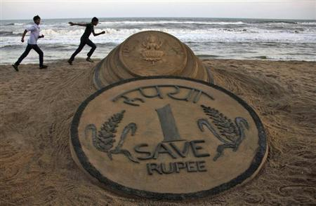 Boys run near a sand sculpture of the Indian Rupee created by Indian sand artist Sudarshan Pattnaik at golden sea beach at Puri in the eastern Indian state of Odisha August 22, 2013. REUTERS/Stringer