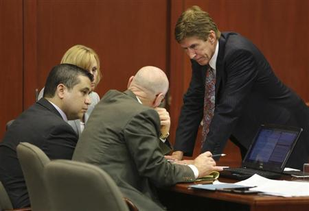 George Zimmerman confers with his defense counsel, Mark O'Mara (R), Don West (2nd R), and Lorna Truett (background) after working out the wording of instructions for a possible charge of manslaughter during the trial of George Zimmerman in the shooting death of Trayvon Martin at the Seminole County Criminal Justice Center, in Sanford, Florida, July 13, 2013. REUTERS/Joe Burbank/Pool
