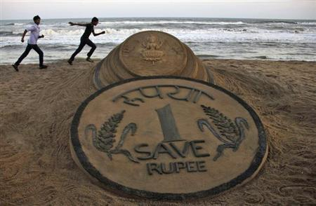 Boys run near a sand sculpture of the rupee created by sand artist Sudarshan Pattnaik at golden sea beach at Puri in Odisha August 22, 2013. REUTERS/Stringer/Files