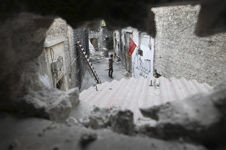 A Free Syrian Army is pictured through a hole in the old city of Aleppo August 27, 2013. REUTERS/Muzaffar Salman