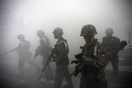 South Korean soldiers walk through smoke as they take part in an anti-terror and security drill at the Integrated Government Complex in Sejong, south of Seoul, in this April 17, 2013 file photo. REUTERS/Kim Hong-Ji/ Files