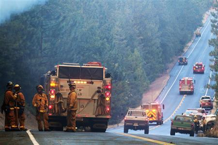 Fire crews line up along Highway 120 at the Rim Fire in this undated United States Forest Service handout photo near Yosemite National Park, California, released to Reuters August 27, 2013. REUTERS/Mike McMillan/U.S. Forest Service/Handout via Reuters