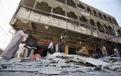 Люди на месте взрыва бомбы в Багдаде 28 августа 2013 года. По меньшей мере 51 человек погиб, десятки получили ранения в результате серии взрывов и стрельбы в Багдаде в среду, сообщили источники в полиции и медицинских кругах. REUTERS/Saad Shalash