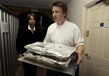 Celebrity chef Jamie Oliver (C) carries out food for a G20 leaders dinner at Downing Street in London April 1, 2009. REUTERS/Christopher Furlong/Pool