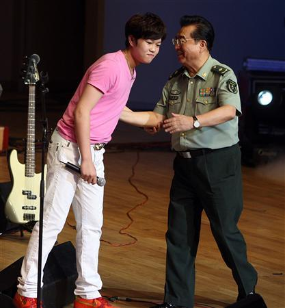 Li Tianyi and his father Li Shuangjiang, a general of the Chinese People's Liberation Army who gained fame singing revolutional songs, are seen at the son's solo concert at a odeum of China National Orchestra in Beijing, August 19, 2011. REUTERS/Stringer
