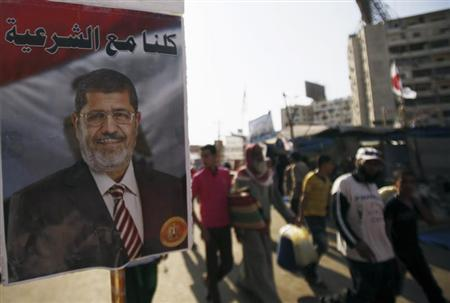 A poster of deposed Egyptian President Mohamed Mursi is seen as members of the Muslim Brotherhood and supporters of Mursi walk at Rabaa Adawiya Square, where they are camping, in Nasr City, east of Cairo August 7, 2013. REUTERS/Amr Abdallah Dalsh