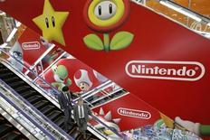 Мужчины едут на эскалаторе на фоне рекламы Nintendo Co в магазине электроники в Токио 23 апреля 2013 года. Японский производитель видеоигр Nintendo Co к новогодним праздникам запустит в продажу новую портативную игровую консоль и на $50 снизит цену на устройство Wii U в версии с 32 гигабайтами памяти в Северной Америке и Европе, пытаясь повысить скромные объемы продаж. REUTERS/Toru Hanai