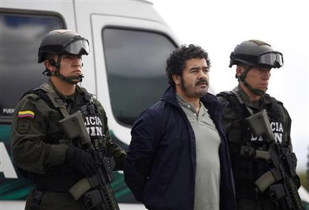 Colombian National Police escort Diego Perez Henao, also known as ''Diego Rastrojo'', suspected leader from International drug gang ''Los Rastrojos'' who was deported from Venezuela, during a news conference at the military base in Bogota July 25, 2012. REUTERS/John Vizcaino