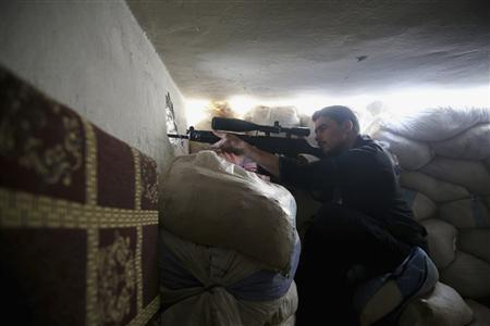 A member of the 'Ahrar Dimachk' Brigade, part of the 'Asood Allah' Brigade which operates under the Free Syrian Army takes aim on one of the battlefronts in Jobar, Damascus August 25, 2013. REUTERS/ Mohamed Abdullah