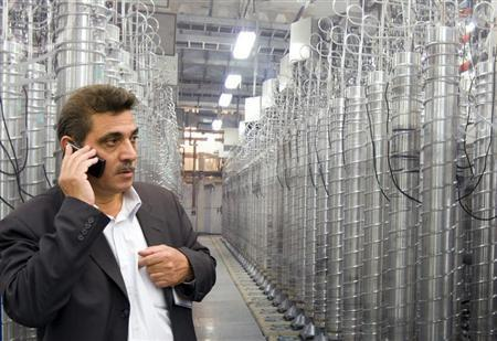 An official from Iran's Atomic Energy Organization speaks on his mobile phone in front of uranium enriching centrifuges at an exhibition of Iran's nuclear achievements at Shahid Beheshti University in Tehran April 20, 2009. REUTERS/Caren Firouz