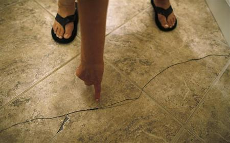 Mary Mahan points to a crack in the floor tile of her home that was a result of an earthquake in Wooster, Arkansas, August 5, 2013. REUTERS/Jim Young