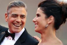"""Ator George Clooney sorri com Sandra Bullock em pré-estreia do filme """"Gravidade"""" nesta quarta-feira. REUTERS/Alessandro Bianchi"""