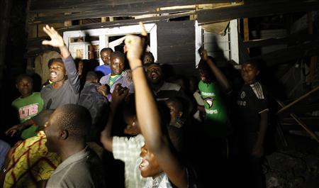 Residents chant slogans as they demonstrate outside the ruins of a house struck by a mortar bomb during an operation in Goma town in the eastern the operation with the Congolese army to drive back M23 rebels from the city of Goma in eastern Congo, a U.N spokesman said. REUTERS/Thomas Mukoya