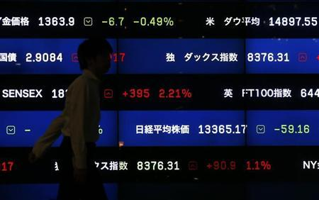 A man walks past a screen showing market indices in Tokyo August 22, 2013. REUTERS/Issei Kato