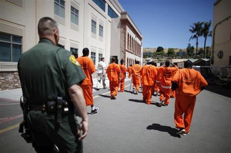 Inmates are escorted by a guard through San Quentin state prison in San Quentin, California, June 8, 2012. REUTERS/Lucy Nicholson