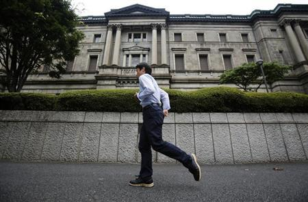 A pedestrian walks past the Bank of Japan headquarters in Tokyo August 8, 2013. REUTERS/Yuya Shino