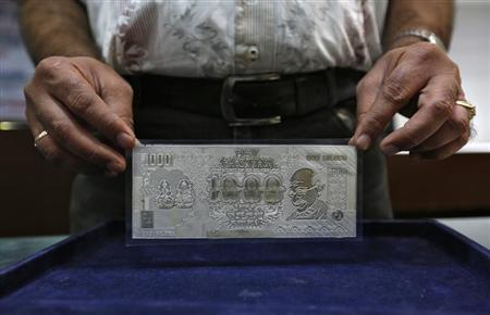 A jeweller poses with a silver plate in the form of an rupee note inside a showroom in New Delhi August 19, 2013. REUTERS/Mansi Thapliyal/Files