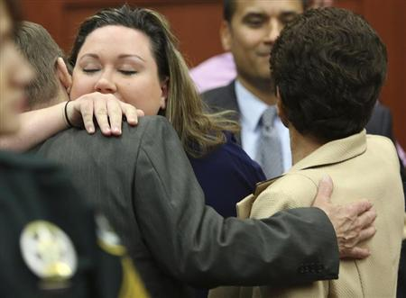 George Zimmerman's wife, Shellie (2nd L), hugs her Father-in-law Robert Zimmerman Sr. (L) and after her husband was found not guilty in the 2012 shooting death of Trayvon Martin at the Seminole County Criminal Justice Center in Sanford, Florida, July 13, 2013. REUTERS/Gary W. Green/Pool