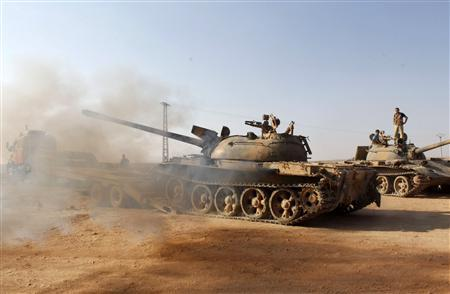 Free Syrian Army fighters drive a military tank that belonged to forces loyal to Syria's President Bashar Al-Assad after they seized it, in Aleppo's town of Khanasir August 29, 2013. REUTERS/Molhem Barakat