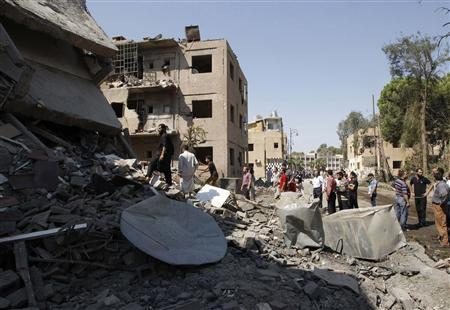 People look at the damage at a site hit by what activists say was a car bomb in Raqqa province, eastern Syria August 29, 2013. REUTERS/Nour Fourat