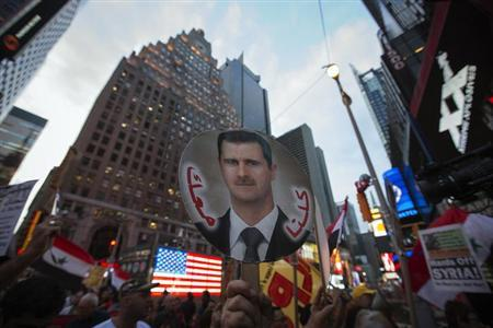 Local activists and Syrian-American supporters of Syrian President Bashar al-Assad hold up his image during an anti-war rally in front of a U.S. Armed Forces Recruiting Station in Times Square, New York August 29, 2013. REUTERS/Adrees Latif