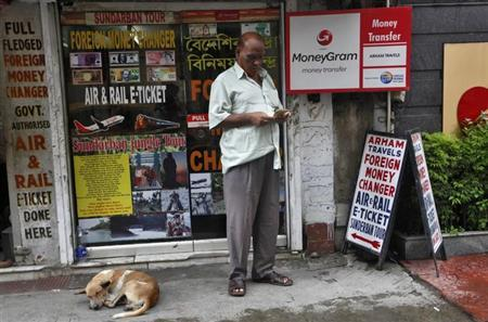 A customer counts currency outside a currency exchange shop in Kolkata August 29, 2013. REUTERS/Rupak De Chowdhuri