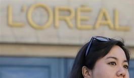 Туристка проходит мимо штаб-квартиры фирмы L'Oreal в Париже, 16 августа 2013 года. Операционная прибыль и рентабельность французского производителя L'Oreal выросли в первом полугодии 2013 года, несмотря на некоторое ослабление спроса на ряде крупных рынков. REUTERS/Christian Hartmann