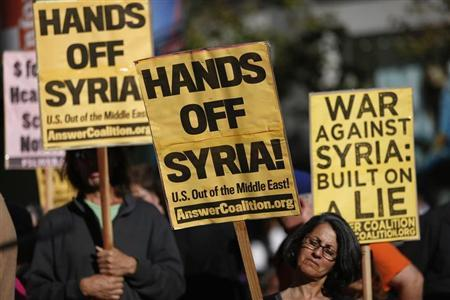 Demonstrators hold signs during a rally in opposition to the proposed military intervention against Syria in San Francisco, California August 29, 2013. REUTERS/Stephen Lam