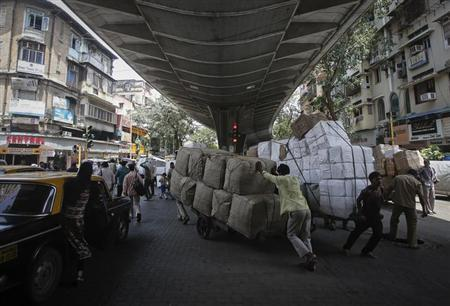 Laboueres move handcarts loaded with goods under a flyover at a market in Mumbai August 30, 2013. REUTERS/Danish Siddiqui
